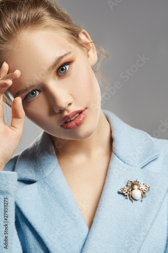 Photo Portrait of lady with tied back fair hair, wearing sky blue coat with brooch in view of bee with transparent crystals on wings