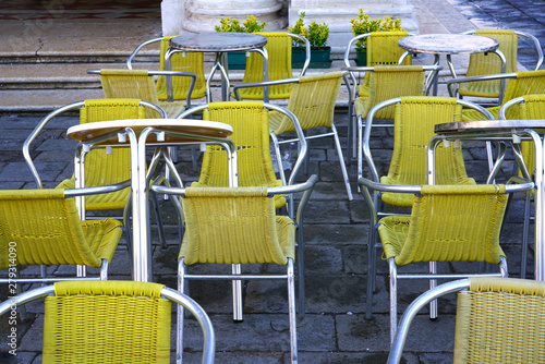 Yellow chairs and tables at an outdoor cafe in Venice, Italy