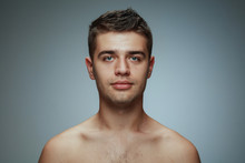 Portrait Of Shirtless Young Man Isolated On Grey Studio Background. Caucasian Healthy Male Model Looking At Camera And Posing. Concept Of Men's Health And Beauty, Self-care, Body And Skin Care.