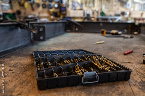 Obraz Metalwork drill bits in plastic tub. A closeup view of a blacksmith's drill bits stored in plastic container on a workbench inside a workshop. Spotting bits used for drilling pilot holes in steel. - fototapety do salonu