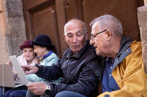Photo anziani seduti davanti a un portone discutono di fronte a un computer