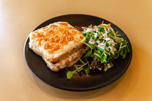 Freshly Served Food In Restaurant. A Close Up Shot Of A Tasty Lunch Served In A Bistro, Consisting Of Croque Monsieur - A Toasted Sandwich Filled With Cheese And Ham, And A Serving Of Fresh Salad