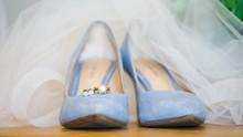 Closeup Of Beautiful Light Blue Female Wedding Shoes Under A White Wedding Dress