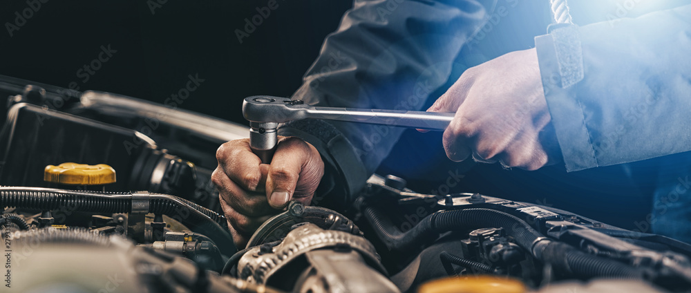 Fototapety, obrazy: Auto mechanic working on car engine in mechanics garage. Repair service. authentic close-up shot, banner size