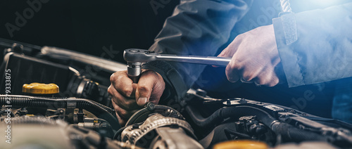 Auto mechanic working on car engine in mechanics garage. Repair service. authentic close-up shot, banner size