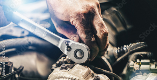 Fotomural  Auto mechanic hands working on car engine in mechanics garage