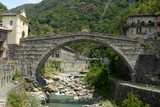 Overview of the ancient Roman bridge at sunset in the town of Pont St Martin in the Aosta Valley - Italy