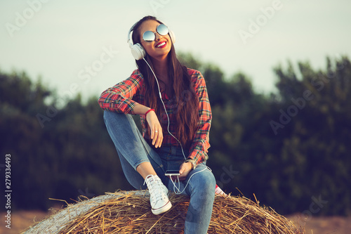 Poster de jardin Magasin de musique Beautiful girl sitting on a haystack, listening to music , enjoying sunset.