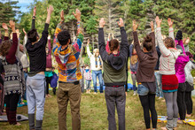 Fusion Of Cultural & Modern Music Event. A Gathering Of People Are Seen Standing In A Ring To Face Each Other As They Perform Yoga Stretches At A Festival Campsite In Nature, Relaxing Together.