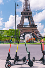 Scooter On The Street Of Paris. Car Rental. Youth Trends And Fashion Technology. The Eiffel Tower.