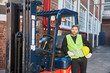 Forklift driver with forklift in front of the warehouse