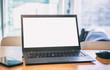 Blank screen laptop on a wooden desk, blur winddow background