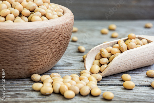 Dried raw soya in wooden bowl and measuring cup on wooden background Canvas Print