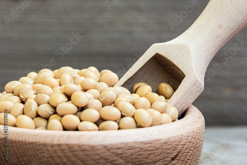 Obraz na plátne Dried raw soya in wooden bowl and measuring cup on wooden background