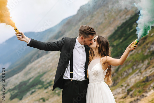 Photo  Side view portrait of a lovely married couple kissing in mountains while holding smoking grenades