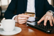 Close up of a male hand dressed in suit holding a gold credit card while sitting on a table with a laptop.