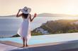 canvas print picture - Attraktive Frau in weißem Sommerkleid genießt den Sonnenuntergang am Pool mit einem Aperitif in der Hand