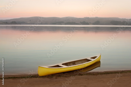 Yellow canoe on the shore of Tomales Bay at dusk with pastel colors and glassy w Canvas Print