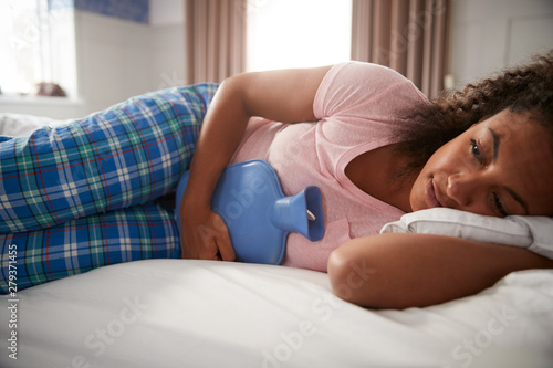 Fotomural  Woman Wearing Pajamas Suffering With Period Pain Lying In Bed With Hot Water Bot