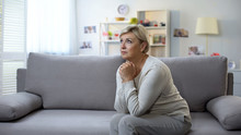 Depressed Mature Woman Praying, Sitting On Sofa, Life Difficulties And Crisis
