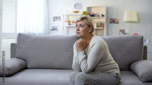 Fotografía  Depressed mature woman praying, sitting on sofa, life difficulties and crisis
