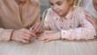 Young mother doing manicure for daughter, spending time together, female leisure