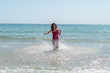 Young woman running through the sea and having a good time