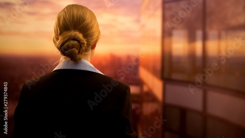 Fototapety, obrazy: Young businesswoman standing on terrace of business center, enjoying sunset