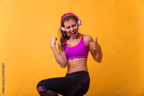 Cheerfully smiling mixed race sporty woman gains victory, isolated on orange  background - 279376857