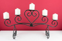 White Candle On A Red Background In A Wrought Iron Candle Holder.