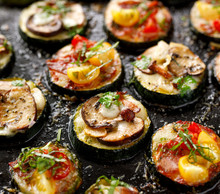 Zucchini Pizza Bites From Zucchini Slices With The Addition Of Brown Mushrooms, Mushroom Chanterelles, Mozzarella Cheese, Salami Sausage, Cherry Tomatoes And Herbs On A Black Background, Close-up.