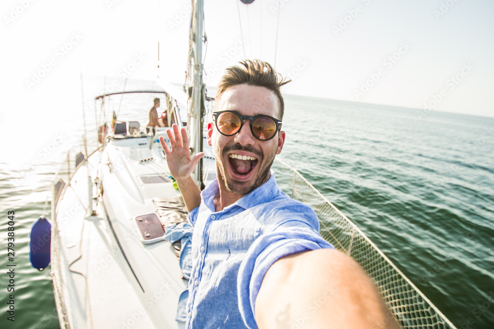 Fototapeta Handsome caucasian man taking a selfie on a exclusive luxury sailing boat at vacation