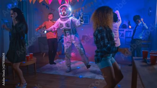 At the College House Costume Party: Fun Guy Wearing Space Suit Dances Off, Doing Robot Dance Modern Moves. With Him Beautiful Girls and Boys Dancing in Neon Lights. - 279388614