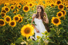 Beautiful Woman In Hat Poses In Field Of Sunflowers