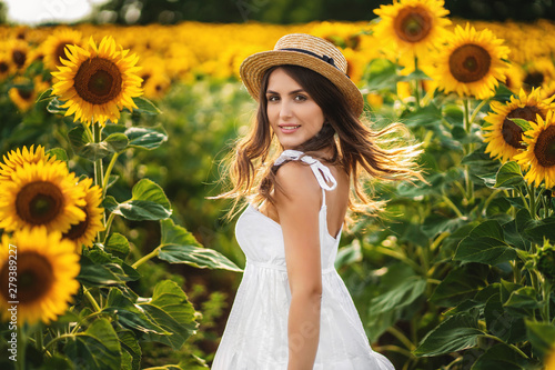 Portrait of a smiling woman in a straw hat. field with blooming sunflower at background