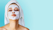 canvas print picture Beautiful young woman with facial mask on her face. Skin care and treatment, spa, natural beauty and cosmetology concept.