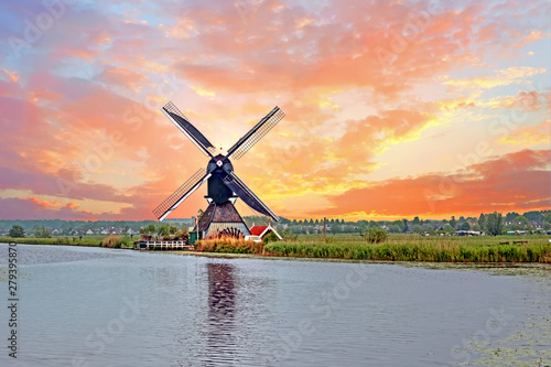 Aerial from a traditional windmill in the countryside from the Netherlands at sunset