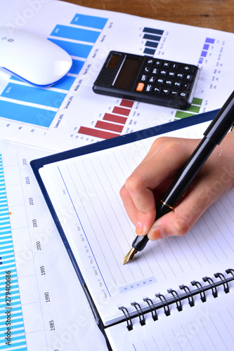 Hand writing on blank notebook with graph, chart, keyboard, mouse and calculator on wooden table - 279400686