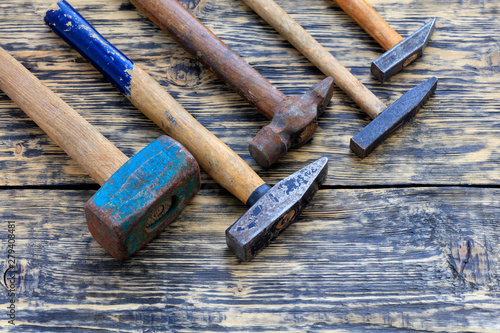 Old iron hammers lie on a wooden table. Canvas-taulu