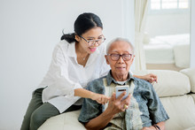 Elderly Man Using A Phone With...