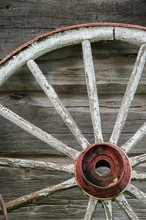 Old Wooden Wagon Wheel Leaning Against Log Cabin