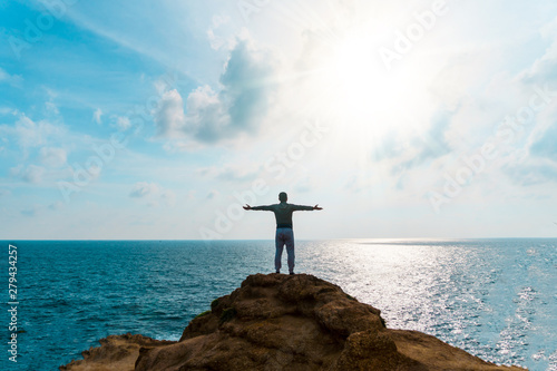 Fototapeten See sonnenuntergang Man rise hands up to sky freedom concept with blue sky and summer beach background.