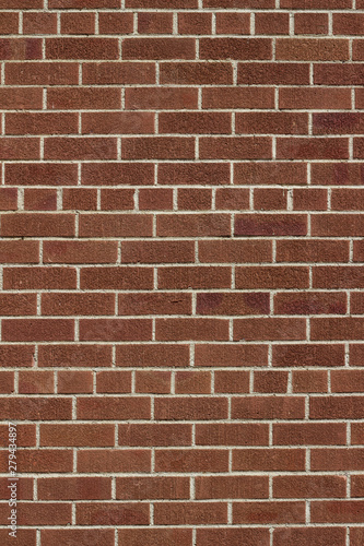 Modern brown color brick wall background with weathered rough texture bricks in a common bond brickwork pattern