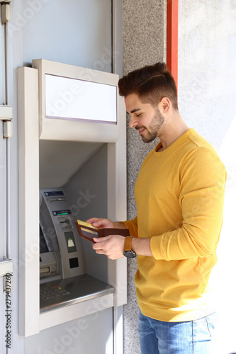 Obraz na plátne Young man with credit card near modern cash machine outdoors