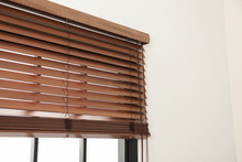 Modern Window With Stylish Wooden Blinds Indoors. Space For Text