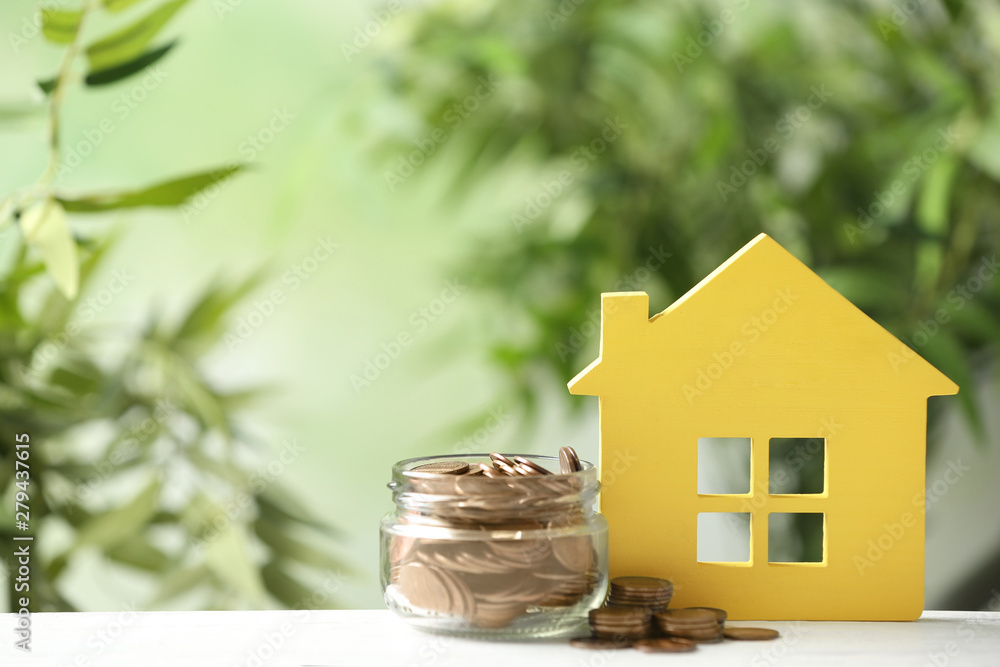 Fototapety, obrazy: Model of house and jar with coins on table against blurred green background. Space for text