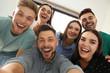 Group of happy people taking selfie in office