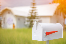 White Mailbox In Front Of House Background During Early Morning Light