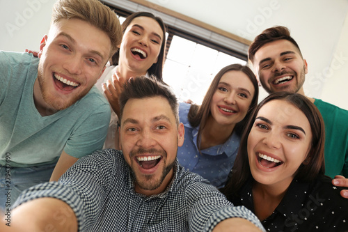 Group of happy people taking selfie in office