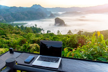 A Laptop, Mobile  On Wooden Table With Sunrise And Mountain Fog Background In Morning. A Start Of New Day. Freelance Business Concept.
